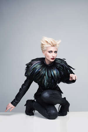 beautiful young model with futuristic leather clothes and feathers posing and looking at camera photo
