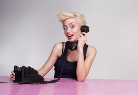 beautiful young woman talking on the phone and looking at camera photo