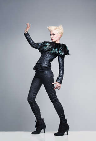 platinum hair: futuristic fashion model rising her hand and psing on a platform on grey background