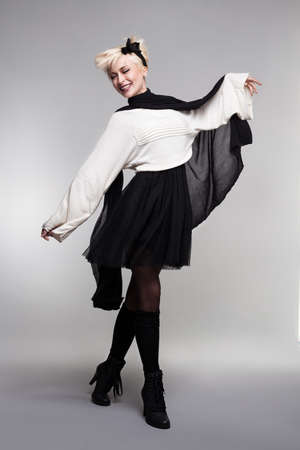 fashion model dancing smiling and posing on gray background photo