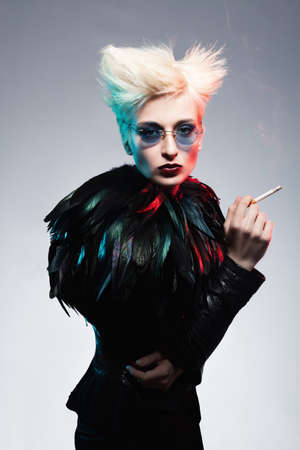 platinum hair: fashion model wearing leather costume with feathers holding a cigarette in her hand on blue background