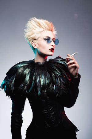 punk hair: futuristic blond fashion model holding a cigarette Stock Photo