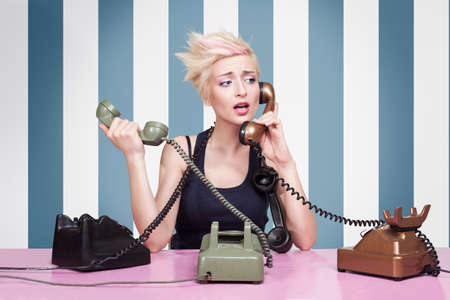 young lady trying to answer the phones on striped background photo