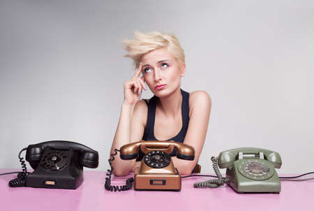 young lady sitting and thinking on a pink desk with colorful antique phones photo