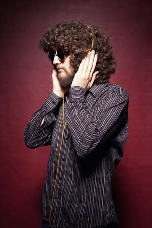 young casual man with long curly hair listening music with headphone on red background photo