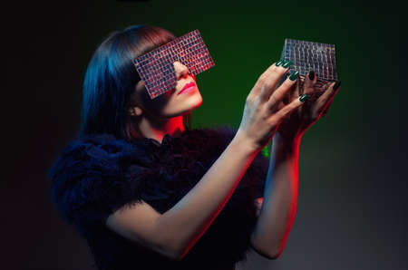 futuristic concept with a model holding an object and trying to identify it on dark background photo