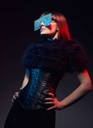 futuristic concept with a model wearing a glasses made of mirror pieces and posing on dark background photo