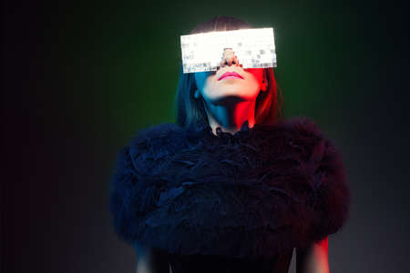 futuristic model wearing a weird glasses looking at a light source on dark background photo