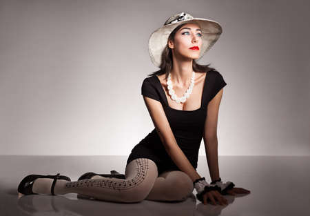 young lady wearing a retro style lace hat looking away on grey background photo