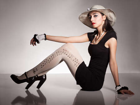 patent leather: young model with lace hat and knitted wristbands sitting on reflective surface and looking at camera on grey background