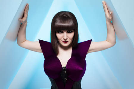 portrait of a young brunette model in futuristic clothes made of paper and leather looking at camera on blue background photo