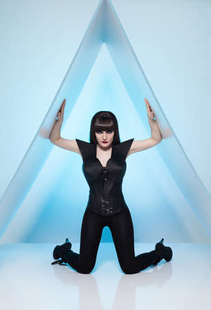 young beautiful woman in a futuristic costume posing on a triangle platfrom on blue background photo