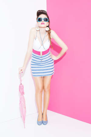 ratty: young stylish lady with pin up style holding an umbrella and posing on white-pink background