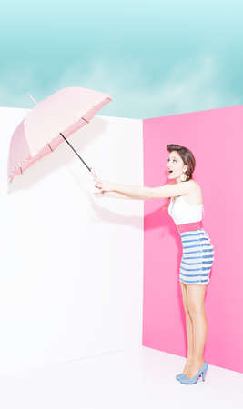 mini umbrella: pin up girl trying to hold an umbrella on white and pink background  Stock Photo