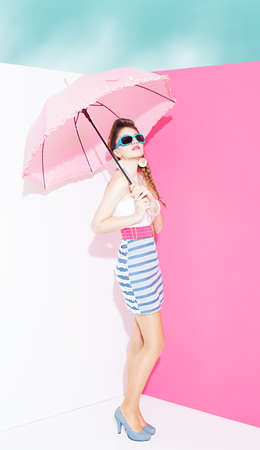 mini umbrella: stylish young lady holding an umbrella and standing on the corner of an interior without roof