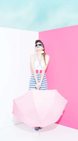 ratty: pin up style lady holding a dotted pink umbrella on the vorner of an pink white room without a roof Stock Photo