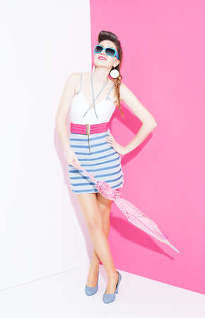 ratty: pin up style fashion model with an umbrella looking up and posing on white pink background
