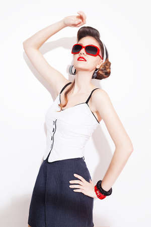 nifty: young beautiful fashion model with pin up style and red accessories posing on white background Stock Photo