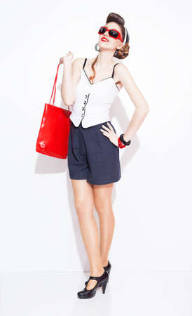 heel strap: pinup style fsahionable lady carrying a red leather handbag posing on white background
