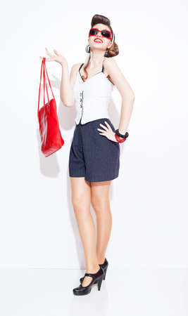 fashionable lady with pinup style holding a red leather bag smiling and posing on white background photo