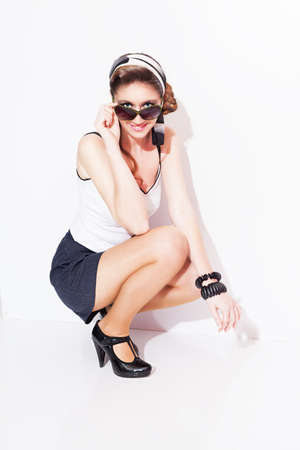 heel strap: colorful pin up style fashion model holding her glasses and smiling on white background Stock Photo
