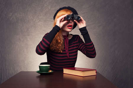 young ginger woman using binoculars found something interesting on grunge background photo