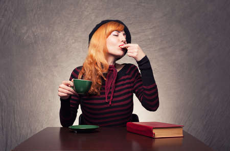 beautiful ginger lady eating a cookie and drinking tea or coffee on grunge background photo
