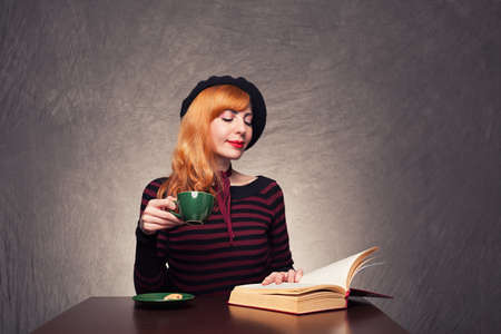 young girl sitting and a reading a book while drinking her coffee on grunge background photo