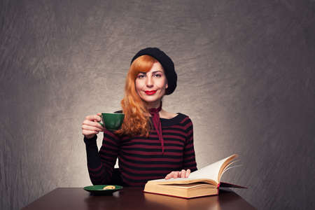 cute lady with beret sitting and looking camera with a coffee on her hand on grunge background photo