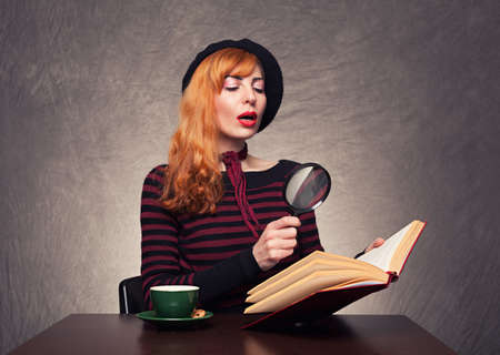 beautiful ginger model reading a book with her magnifying glass on grunge background photo