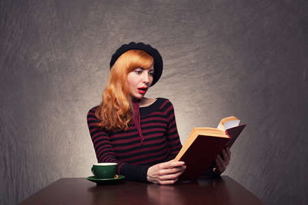 amazed young lady reading a exciting book on grunge background photo