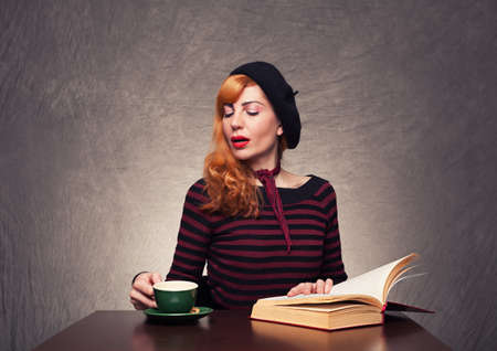 beautiful young lady reading a book and drinking coffee or tea on grunge background photo