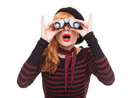 portrait of a surprised young lady using her binoculars isolated on white background photo