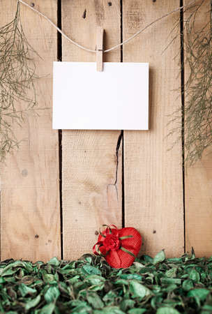 peg board: heart shaped wrapped gift on foliage in front of a wooden wall with a blank paper hanged on