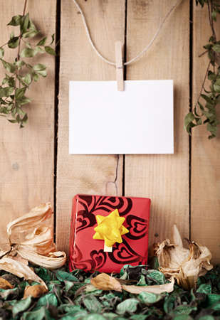 sear and yellow leaf: red gift box on th seared leafage in front of a wooden wall with a blank paper Stock Photo