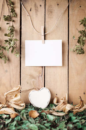 sear: white wooden heart with sear flowers and leafage in front of a wooden wall with a blank paper hanged on Stock Photo