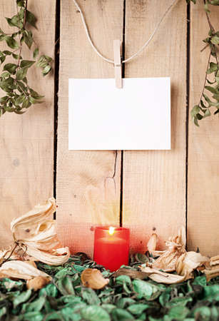 still life with candle, seared leafage and flowers and a blank paper hanged on a wooden wall photo