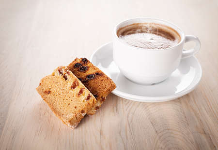 rebanada de pastel: pastel en rodajas y una taza de café en la mesa de madera