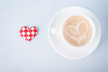 cup of coffee and a little checked heart on blue background Stock Photo
