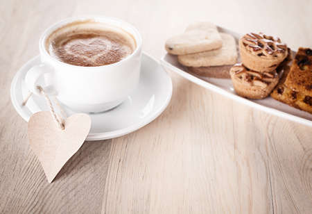 cup of coffee with a blank heart shped note and cookies on wooden table photo