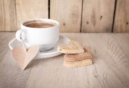 hot coffee with a not paper and heart shaped cookies on wooden background