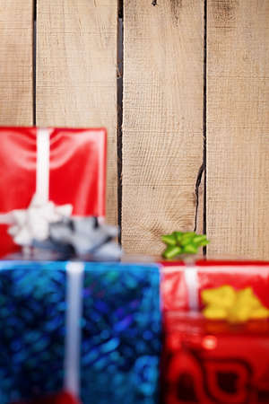 a lot of gift colorful gift packages and ribbons in front of a wooden wall focus is on the wall  photo