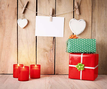 burning candles and gift boxes in front of a wooden wall with hearts and blank paper photo
