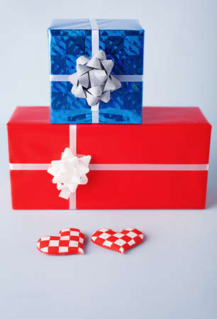 two identical hearts and two different gift boxes on blue background photo