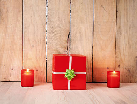 two candles and a red gift box in front of a wooden wall photo