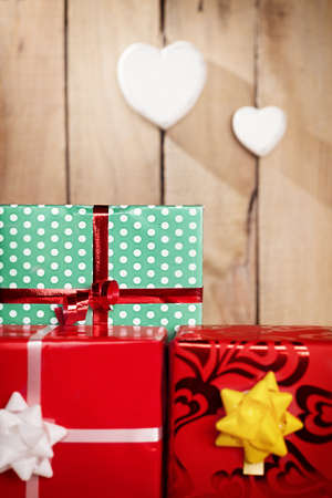 colorful gift packages in front of a wooden background with two heart hanged.shallow depth of field.focus is on green package photo