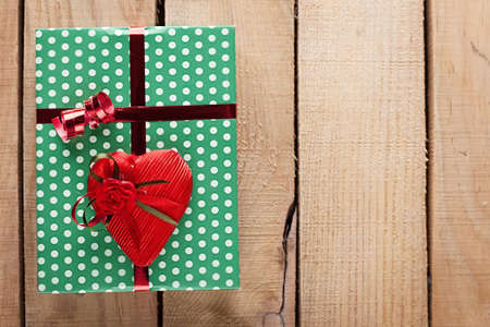 green gift box and a heart on wooden background photo