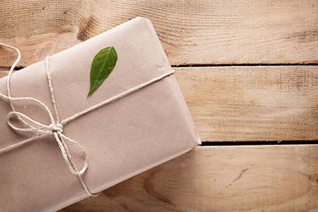 package shipment: gift box with a green leaf on it on wooden background Stock Photo
