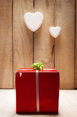 paquete de regalo rojo en frente de una pared de madera con el corazón dos ahorcado Foto de archivo - 19602030
