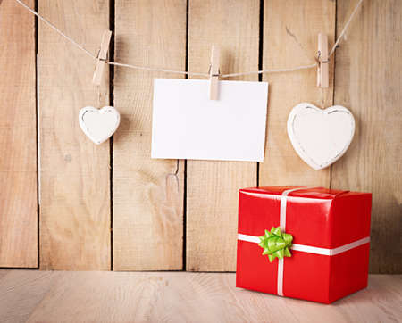 red gift box with green ribbon in front of a wooden wall with hearts and a blank paper photo